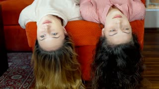 Girls lying with their heads down and chatting with each other, steadycam shot