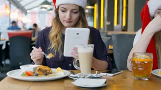Girls using electronics while eating desserts and wearing Santa's hats, steady