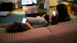 Girls using smartphones and chilling on the sofa