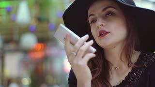 Glamorous woman holding smartphone and talking on loudspeaker
