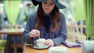 Glamorous woman using spoon to mix the coffee in the cafe