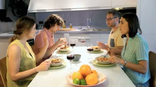 Group of friends chatting while eating dinner in the flat