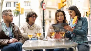 Group of friends talking in the cafe and woman showing something on tablet