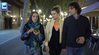 Group of friends walking at night in the city, steadycam shot