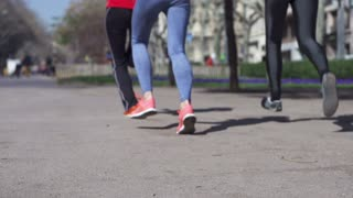 Group of people jogging in the city, slow motion shot at 120fps, steadycam shot