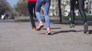 Group of people jogging in the city, slow motion shot at 240fps, steadycam shot