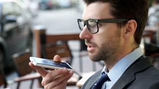 Handsome businessman holding cellphone and talking on loudspeaker, steadycam sho