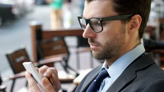 Handsome businessman sitting outdoors and browsing internet on smartphone, stead