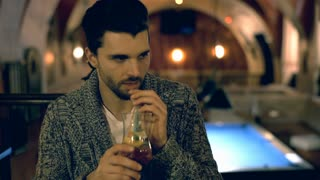 Handsome man drinking alcoholic beverage and smiling to the camera