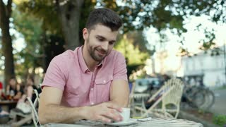Handsome man drinking coffee and eating cookie while smiling to the camera