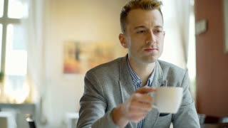 Handsome man in a tweed jacket drinking coffee and smiling to the camera