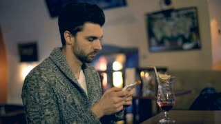 Handsome man in warm jumper sitting in the pub and texting on smartphone
