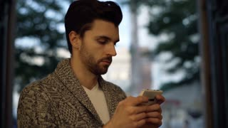 Handsome man in warm jumper smiling to the camera and texting on smartphone