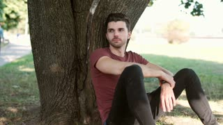 Handsome man leaning on a tree and looking thoughtful in the park