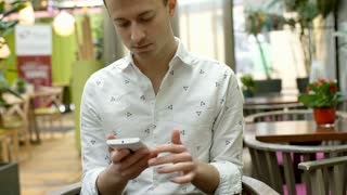 Handsome man sitting in the cafe and texting messages on smartphone, steadycam s