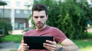 Handsome man sitting in the park and browsing internet on tablet