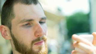 Handsome man sitting outside and browsing internet on smartphone