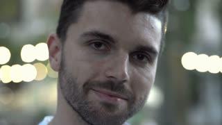 Handsome man smiling to the camera, steadycam shot