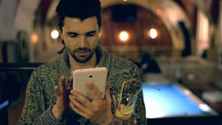 Handsome man using tablet and smiling to the camera in a pub