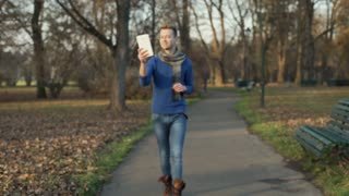 Handsome man walking in the park and having a videocall on tablet, steadycam sho