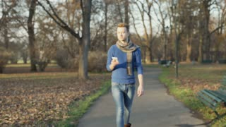 Handsome man walking on pathway and doing selfies on smartphone, steadycam shot