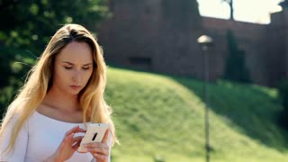 Happy, beautiful girl standing outdoors and texting messages on smartphone