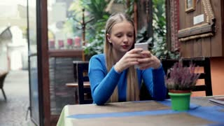 Happy, blonde girl in blue sweater texting on smartphone in the restaurant