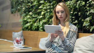 Happy, blonde woman browsing internet on tablet while sitting in the cafe