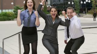 Happy business people showing thumbs, slow motion shot, steadycam shot