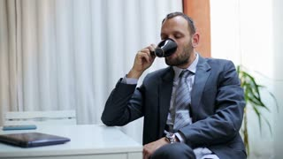 Happy businessman drinking coffee and using laptop.