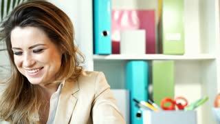 Happy businesswoman sitting in the office, steadycam shot
