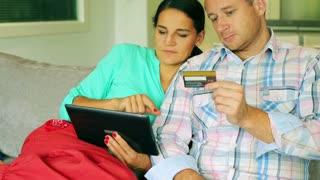 Happy couple doing transaction by the internet and using credit card