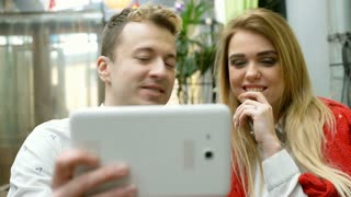 Happy couple having a videocall on tablet while sitting in the cafe, steadycam s