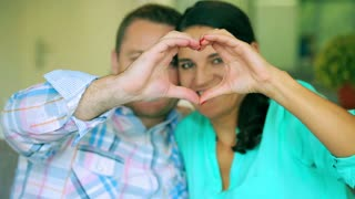 Happy couple making heart to the camera and smiling, steadycam shot