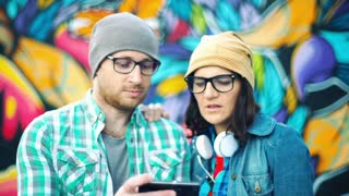 Happy couple of hipsters talking to each other and looking on smartphone