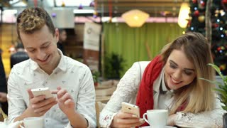 Happy couple sitting in the cafe and browsing internet on smartphones