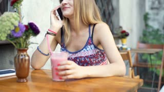 Happy girl chatting on cellphone and drinking cocktail, steadycam shot