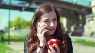 Happy girl chatting on cellphone and looking on bitten apple