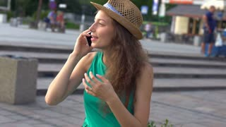 Happy girl chatting on cellphone in the city, steadycam shot, slow motion shot