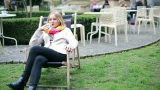 Happy girl drinking orange juice and sitting on sunbed