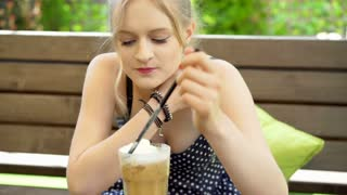 Happy girl eating whipped cream from frappe and enjoying it, steadycam shot