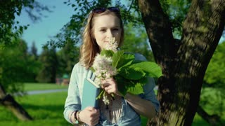 Happy girl holding bunch of flowers and book in the park