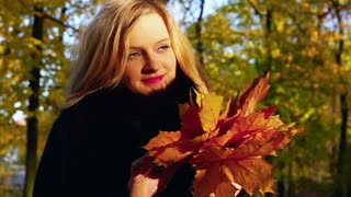 Happy girl holding bunch of maple leaves, slow motion shot at 240fps