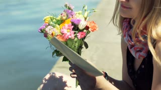 Happy girl holding love letter and bunch of flowers while sitting by the river