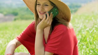 Happy girl in straw hat sitting on the meadow and chatting on cellphone