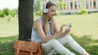 Happy girl listening music and texting on smartphone while sitting on grass