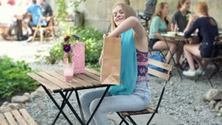 Happy girl looking on her new purchase while sitting in the outdoor cafe