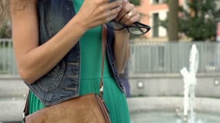 Happy girl looking on smartphone in the city, steadycam shot, slow motion shot