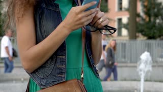 Happy girl looking on smartphone in the city, steadycam shot, slow motion shotas