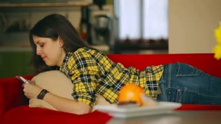 Happy girl lying on the sofa and texting on smartphone, steadycam shot